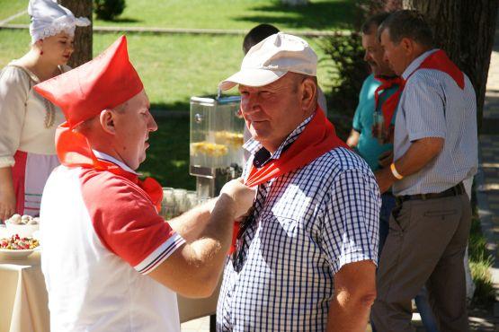 Ведущий мероприятия повязывает пионерский галстук участнику Дня поля