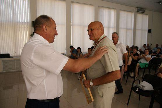 Юрий Ревякин вручает Владимиру Колтунову благодарность