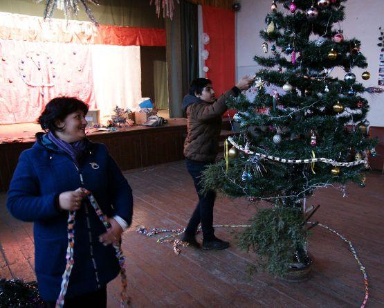 Дима Гайдуков с культорганизатором Еленой Иваненко наряжают зал сельского клуба к предстоящим праздничным мероприятиям. Многие украшения сделаны руками местных ребят