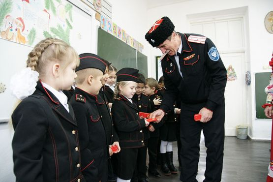Атаман районного казачьего общества Александр Кальницкий вручает красные погоны казачатам